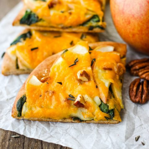 Pieces of Cheddar Apple Pita Pizza with an apple and pecans.