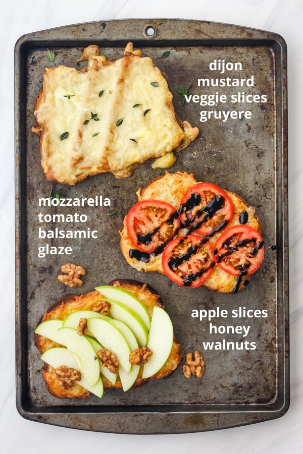 Three toasts on a sheet pan with toppings including apple slices, tomato, and vegetarian sandwich slices.
