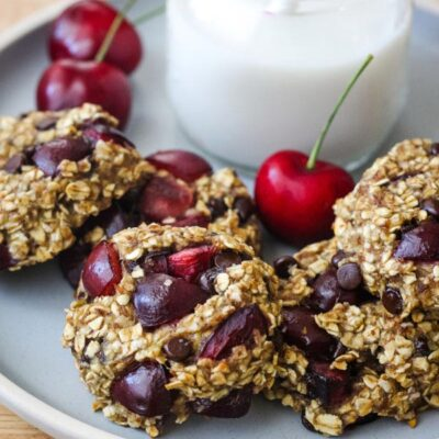 A blue plate with oat cookies, fresh cherries, and a glass of milk.
