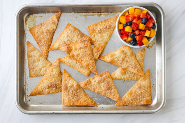 Cinnamon Baked Wonton Chips on a baking sheet with a white ramekin of fruit salsa.