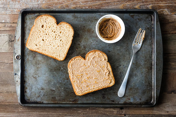 Two slices of bread with a small white bowl of cinnamon butter with a fork.