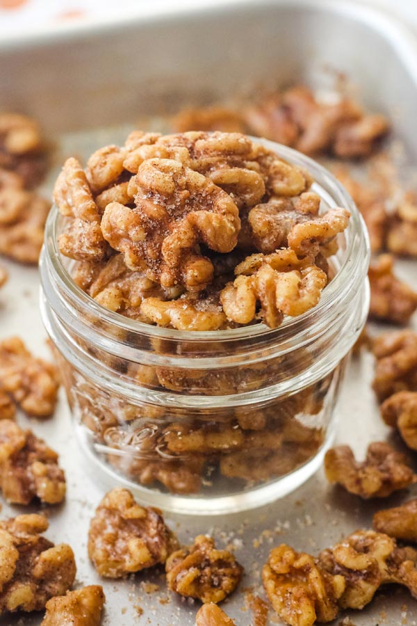 A small mason jar of cinnamon walnuts overflowing onto a sheet pan.