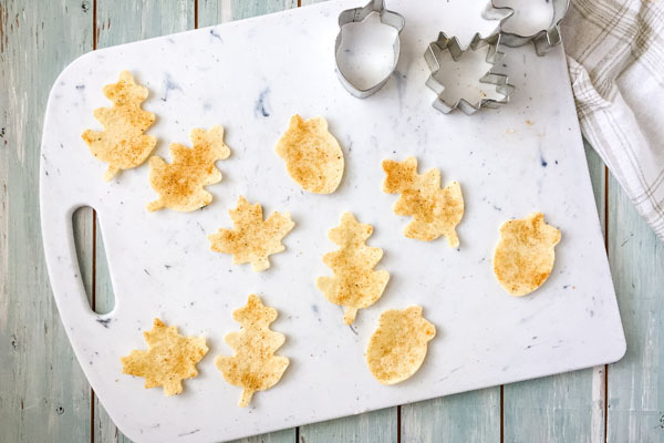 Leaves and acorn tortilla pieces on a cutting board.