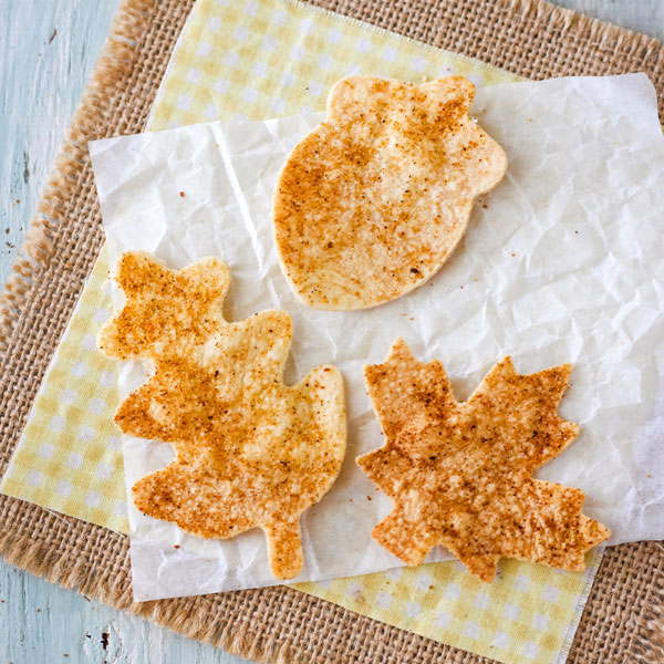Leaf and acorn shaped tortilla chips on a piece of parchment paper.