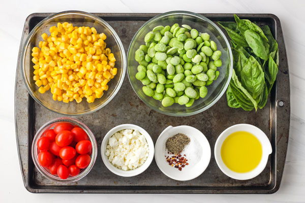 Bowls with corn, edamame, grape tomatoes, feta and basil on a baking sheet.