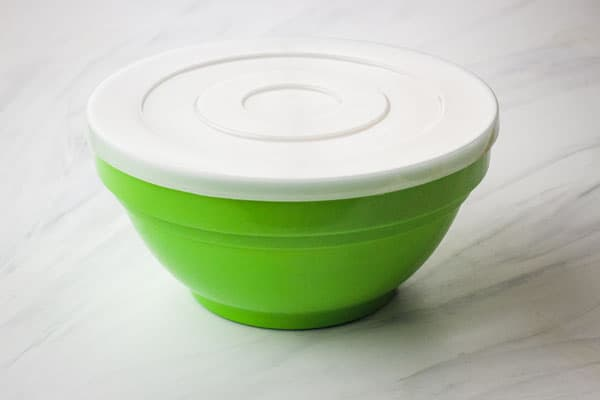 Green mixing bowl covered with a plastic lid.