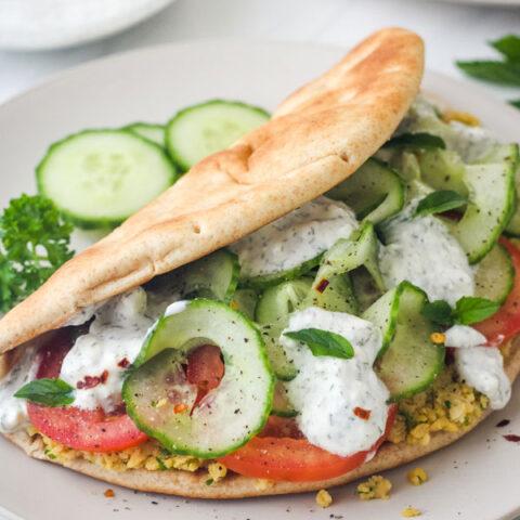 Close up of stuffed pita sandwich on plate.