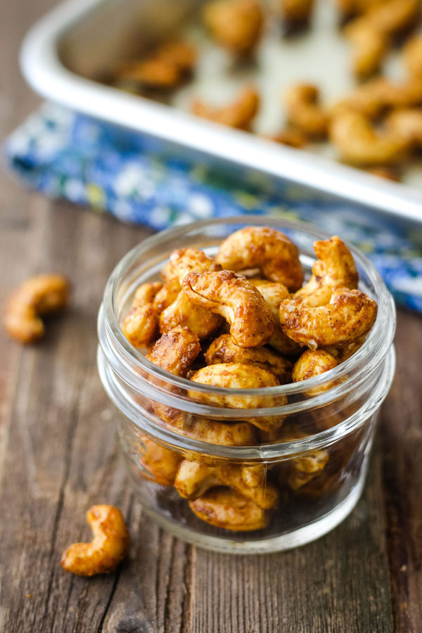Spiced cashews in a small mason jar on a wood table.