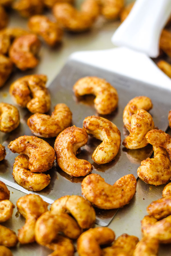 Toasted curry spiced cashews on a metal spatula.