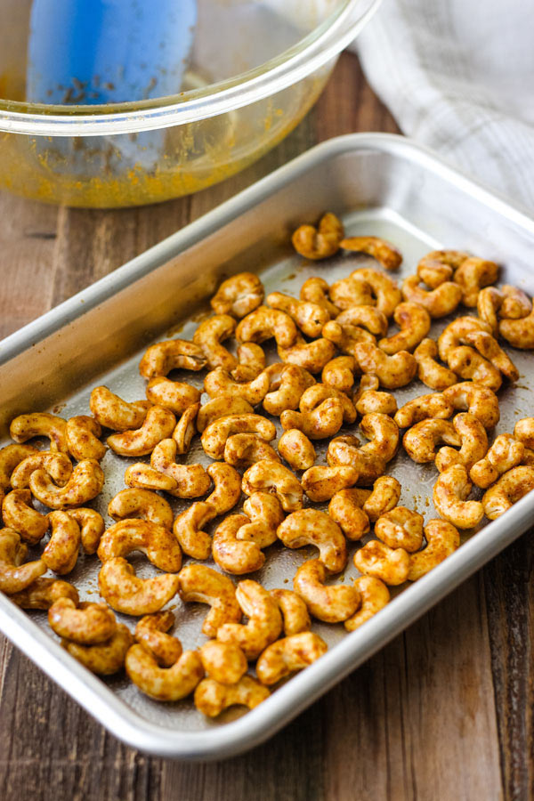 Coated cashews on a small baking sheet.
