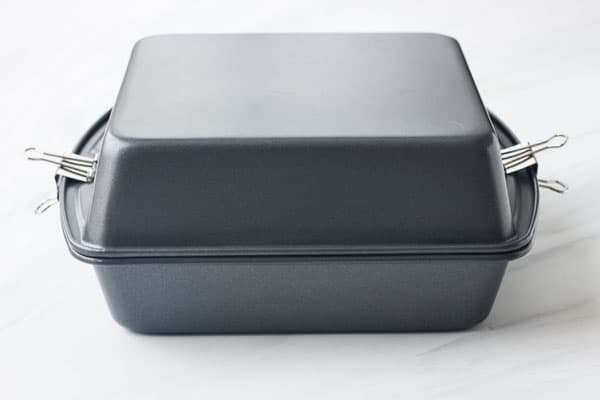 Two square metal pans stacked on top of each other.