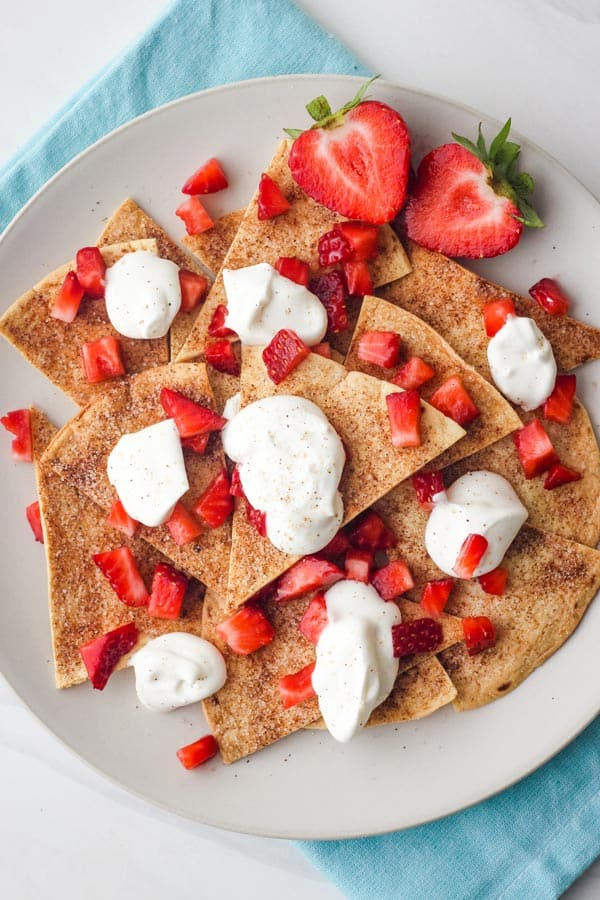 Plate of cinnamon chips topped with whipped cream and chopped strawberries.