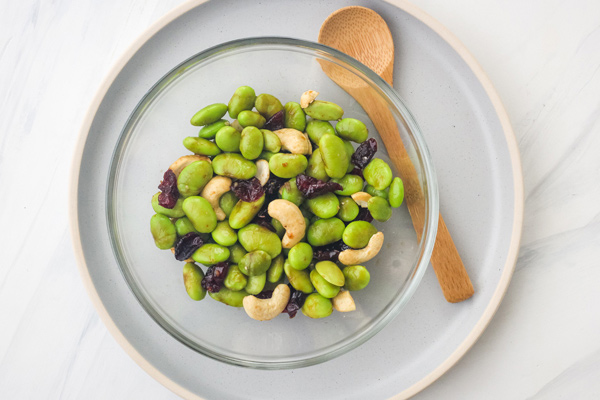 Edamame salad in a glass bowl with a wooden spoon.