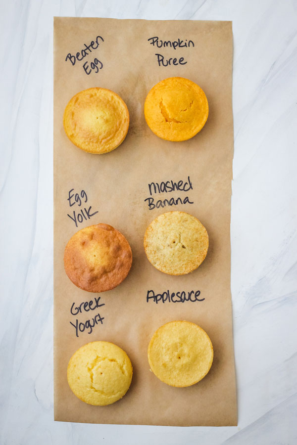Six mini cakes on a piece of paper with the egg substitute used written next to each one.