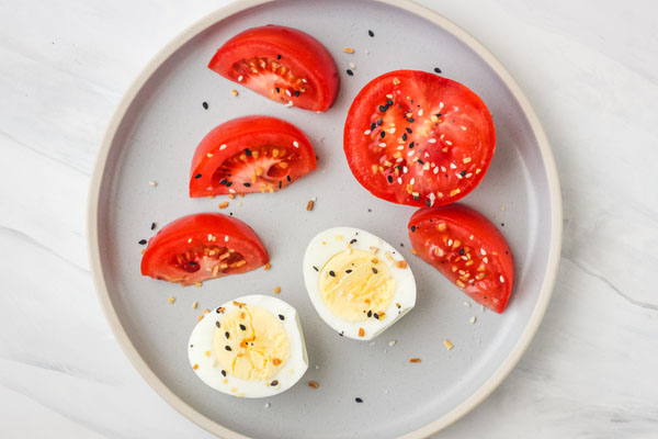 Hard boiled egg and tomato slices on a blue plate.