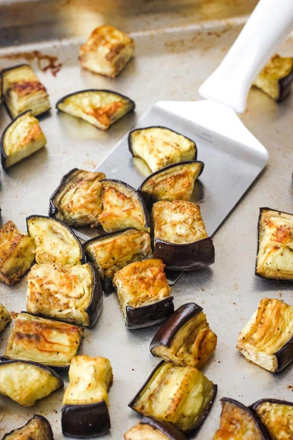 Roasted eggplant pieces on a sheet pan.