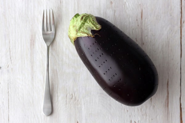 A fork and a fresh eggplant a pattern of stab marks from the fork on it's skin