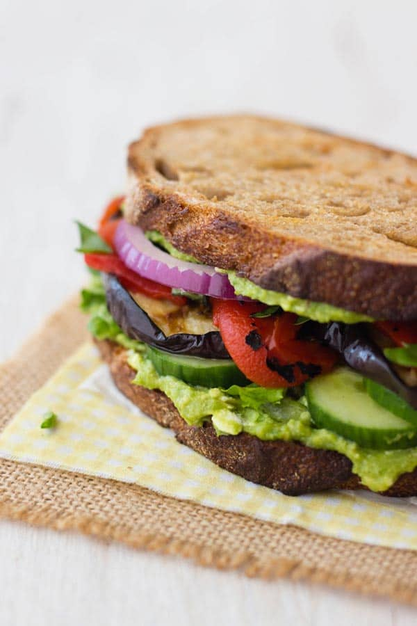 a broiled eggplant sandwich stacked high with layers of vegetables