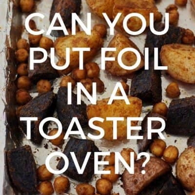 Roasted potatoes and chickpeas on a foil covered baking pan.
