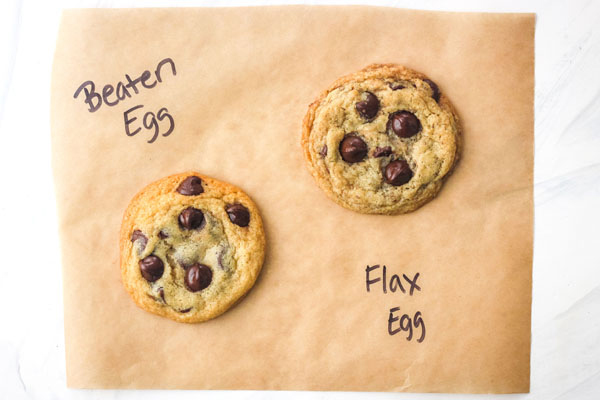 Two cookies on a piece of parchment labeled 'beaten egg' and 'flax egg'