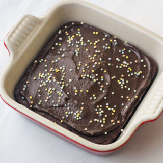 A mini chocolate cake with chocolate frosting and sprinkles in a 5x5 stoneware baking dish.