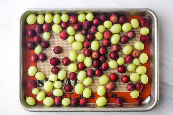 Frozen red and green grapes on a quarter sheet pan.