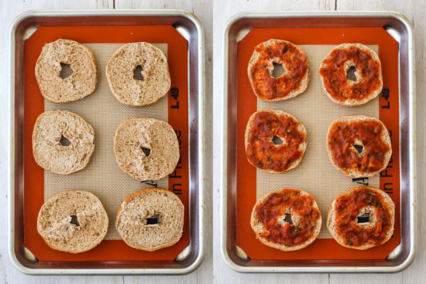 Plain bagels and bagels topped with pizza sauce on a silpat lined sheet pan.