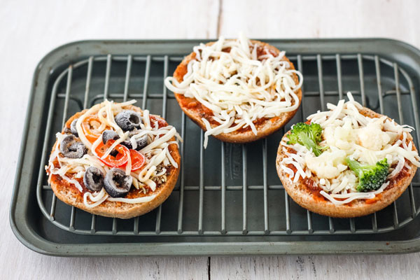 Frozen pizza bagels on a small cooking rack inside a small baking pan.