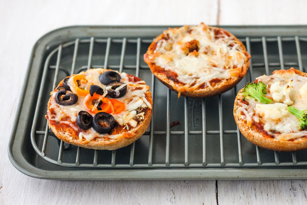 Cooked pizza bagels on a toaster oven rack and pan.