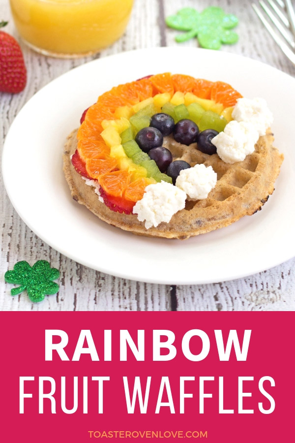 A white place with a waffle topped with fresh fruit in the shape of a rainbow.