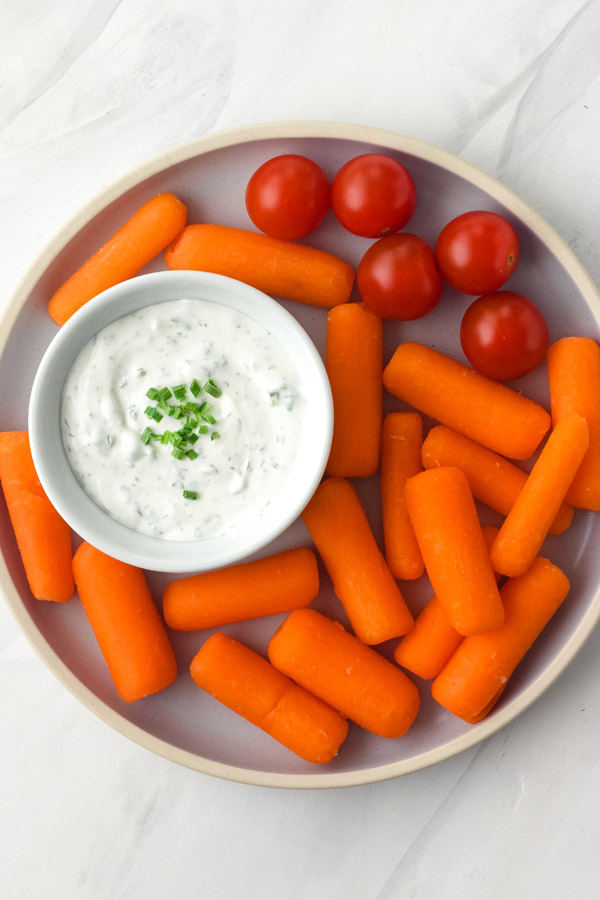 A blue plate with baby carrots, tomatoes, and a white bowl of dip.