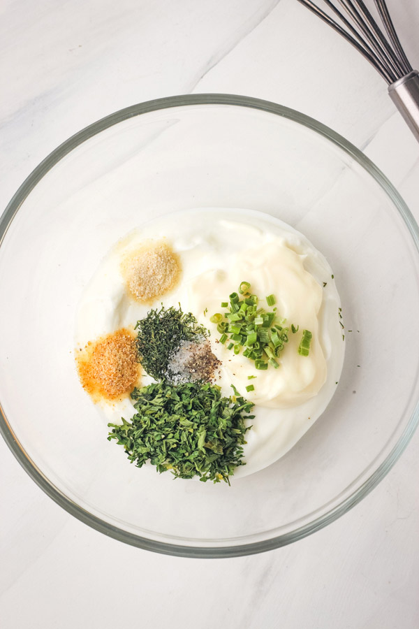 A small glass bowl with yogurt, mayo, herbs and spices.