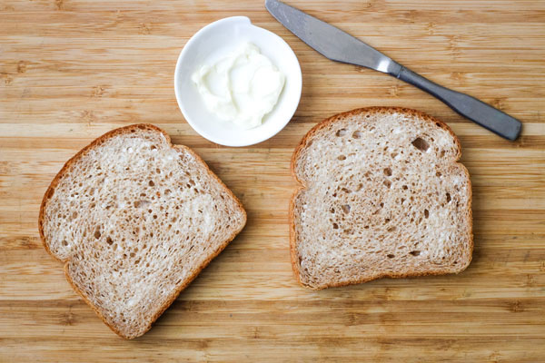 Bread slices spread with mayonnaise on a cutting board.