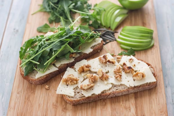 A cutting board with bread slices topped with cheese, nuts and arugula.