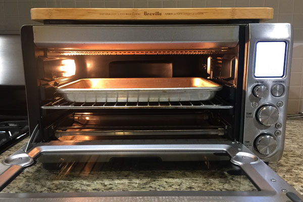 An open toaster oven with a baking pan on the middle rack.