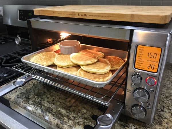 A pan with pancakes and a ramekin of maple syrup warming in a toaster oven.