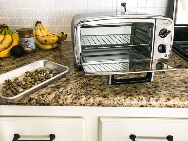Countertop with toaster oven and small sheet pan with nuts.