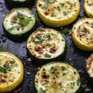 Broiled zucchini and summer squash on a black pan with fresh herbs.