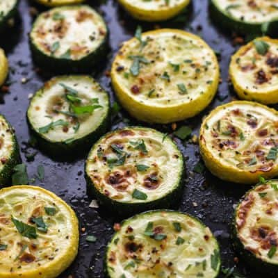Broiled zucchini and squash rounds on a roasting pan.