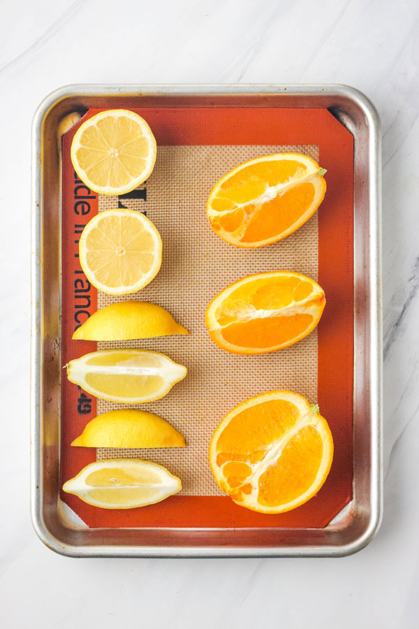 Lemon and orange wedges and halves on a baking sheet lined with a silicone mat.
