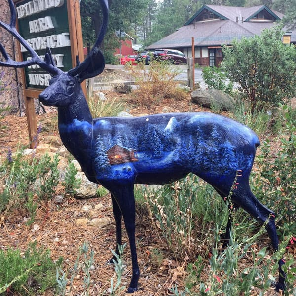 Deer painted with a blue snowy cabin landscape.