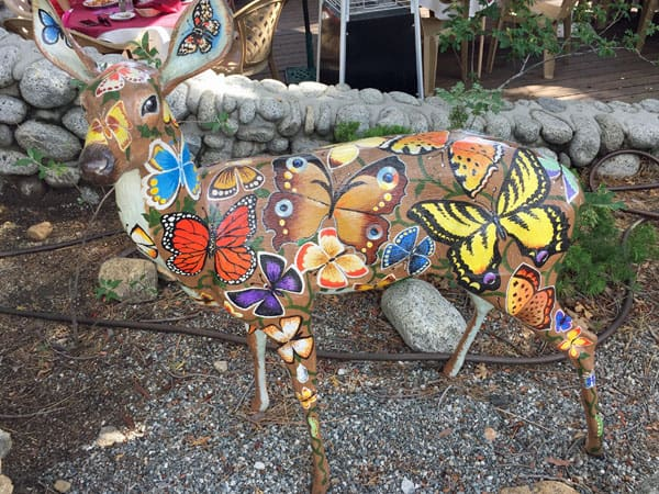 Deer statue painted with colorful butterflies.