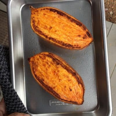 Baked sweet potato halves on an 1/8 sheet pan.