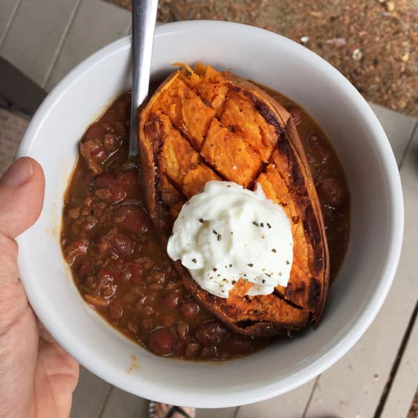 White bowl filled with vegetarian chili, baked sweet potato and Greek yogurt.