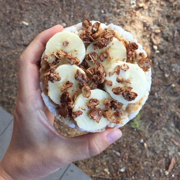 A hand holding a rice cake with peanut butter, banana slices and chocolate granola.