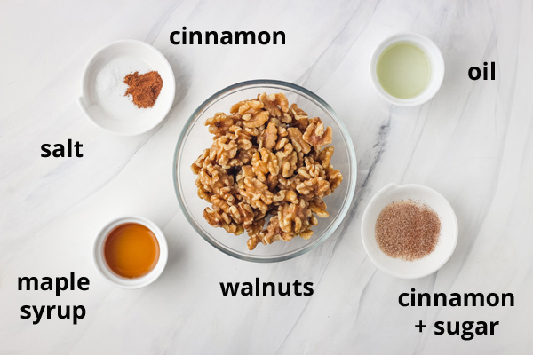 Bowls of walnuts, cinnamon, sugar, maple syrup, and oil on a white table.