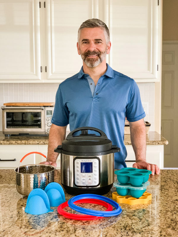 Man standing in a kitchen with a 3-Quart Instant Pot surrounded by accessories.