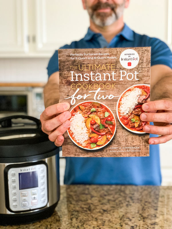 Hands holding the Ultimate Instant Pot Cookbook For Two.