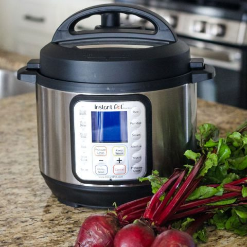 Instant Pot Mini Duo Plus on a kitchen counter with a bunch of beets.