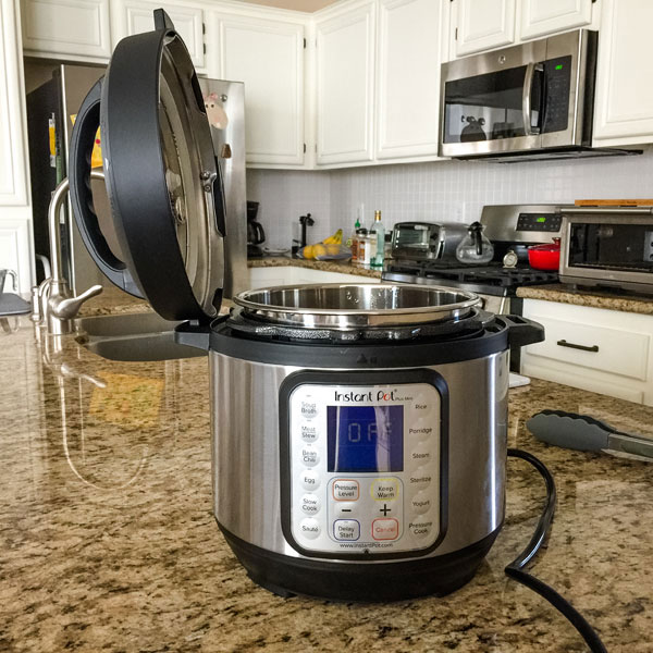 Instant pot on a counter with lid sitting on the side of the machine.